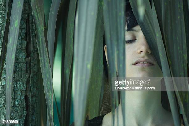 woman standing among palm leaves, eyes closed - sensory perception stock pictures, royalty-free photos & images