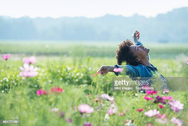 a woman standing among the flowers with her arms outstretched.  pink and white cosmos flowers. - releasing stock pictures, royalty-free photos & images