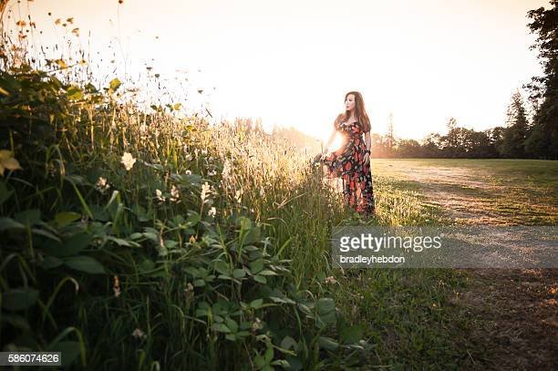Woman standing among wildflowers in meadow at sunset