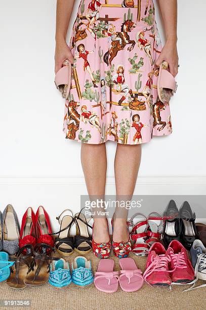 woman standing amongst shoes trying to make a dici