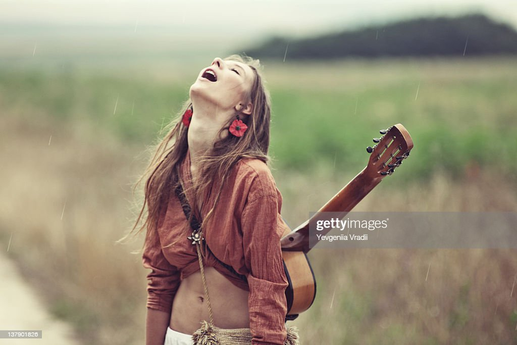 Woman Standing And Carrying Guitar On Her Back Stock Photo