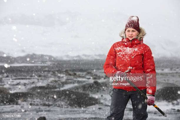 woman standing and holding ice axe close to glacier in iceland - exploration stock pictures, royalty-free photos & images