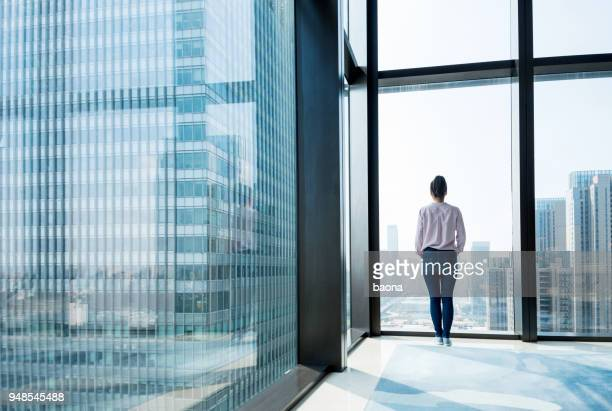 woman standing and looking at cityscape - looking at view stock pictures, royalty-free photos & images