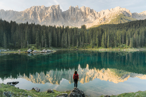 Woman standing and looking at  Lago di Carezza in Dolomites 1038870630