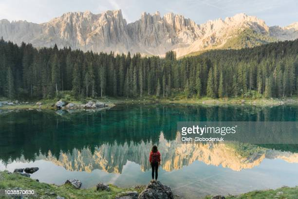 woman standing and looking at  lago di carezza in dolomites - ambientazione tranquilla foto e immagini stock