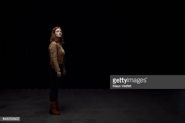 woman standing and looking up in the light - dark stock pictures, royalty-free photos & images