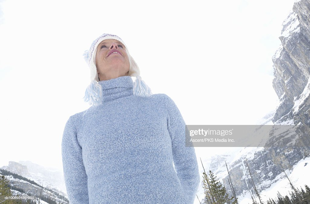 Woman standing and looking upwards, smiling, mountains in background, low angle view : Stockfoto