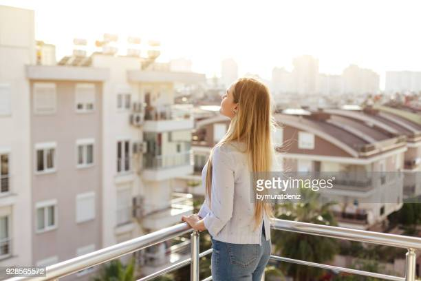 woman standing and relaxing on balcony - balcone foto e immagini stock