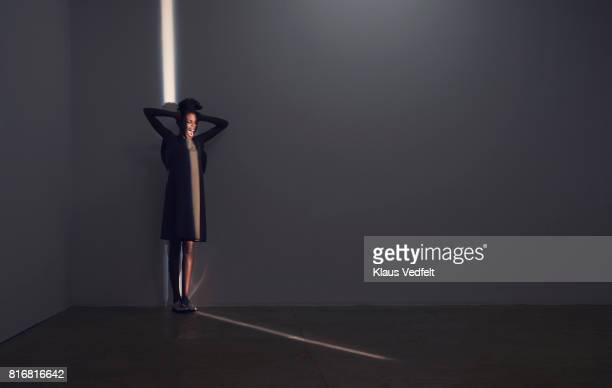 Woman standing and shouting in thin light stripe, in studio with concrete floor