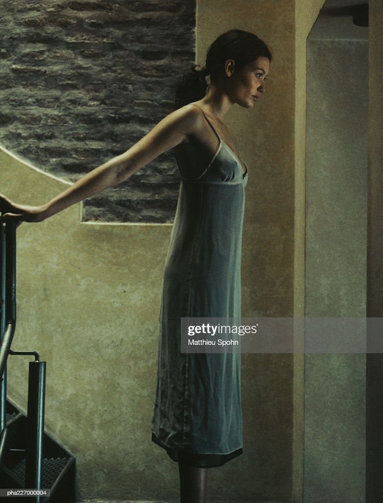 Woman standing, arm extended behind, side view. : Stockfoto