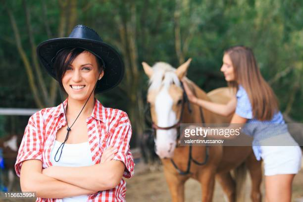 woman standing arms crossed, behind girl preparing horse for ride - female hairy arms stock photos and pictures