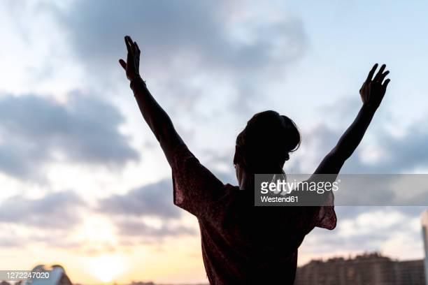 woman standing arms raised watching sunset - 雰囲気 ストックフォトと画像