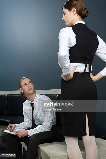 Woman standing as man takes notes