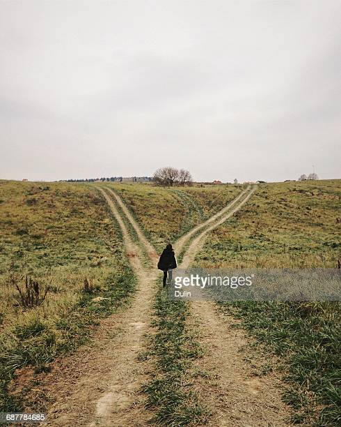 woman standing at a crossroads - crossroad stock pictures, royalty-free photos & images