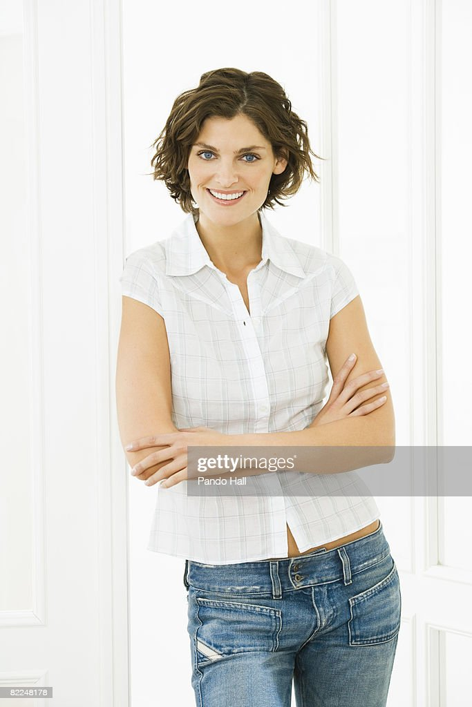 Woman standing at a door, smiling : Stock Photo