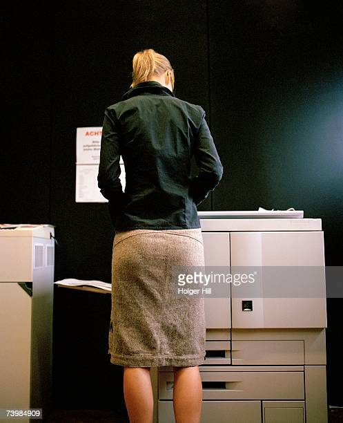 woman standing at a photocopier - skirt stock pictures, royalty-free photos & images