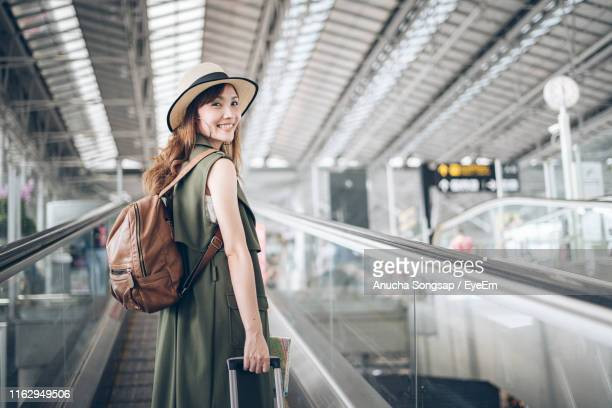 woman standing at airport terminal - casual clothing photos et images de collection