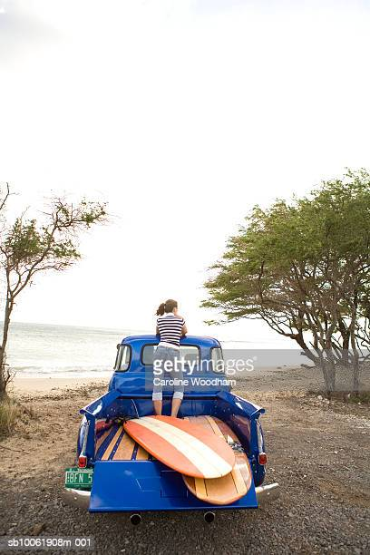 Woman standing at back of pick-up truck with surfboards on beach, rear view