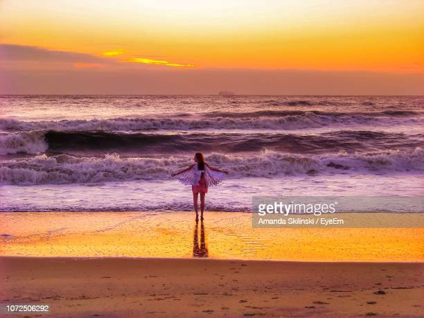 woman standing at beach against sky during sunset - amanda and amanda stock pictures, royalty-free photos & images
