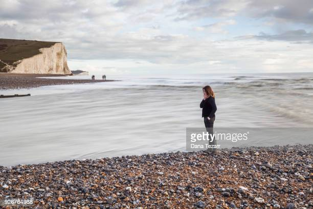 Woman standing at beach where the river Cuckmere floats into the sea with white cliffs in the background
