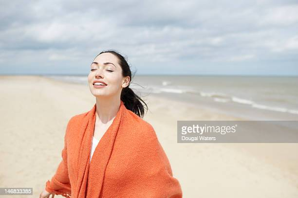 woman standing at beach with eyes closed. - 頭をそらす ストックフォトと画像