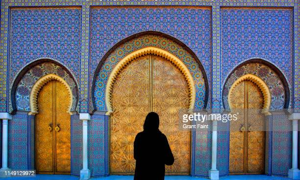 woman standing at brass doors. - marruecos fotografías e imágenes de stock