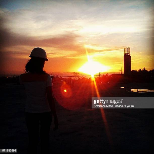 Woman Standing At Construction Site During Sunset