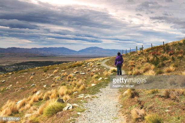 A woman standing at designated walking trail. A concept of travel and explore.