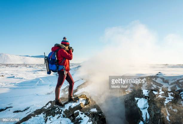 Woman standing at divergent tectonic boundary between North American and Eurasian plates, photographing, Mid-Atlantic Ridge, rift valley, Krafla, Myvatn, Northern Region, Iceland