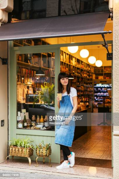 Woman standing at entrance door of a store holding takeaway coffee