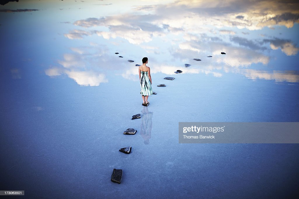 Woman standing at fork in stone pathway in lake : Stock Photo