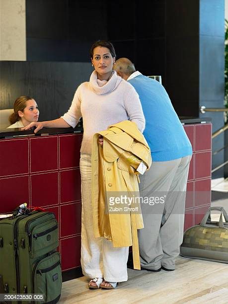 Woman standing at front desk in hotel lobby, man talking to clerk,