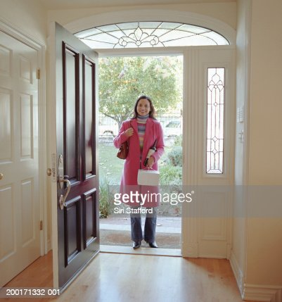 Woman Standing At Front Door Holding Pastry Box Stock