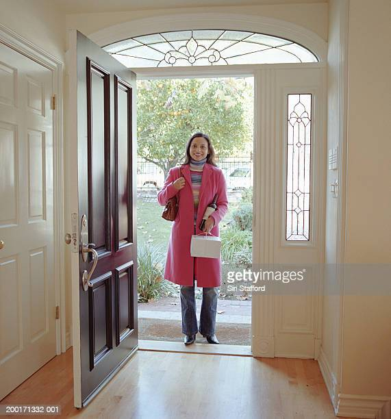 Woman standing at front door, holding pastry box