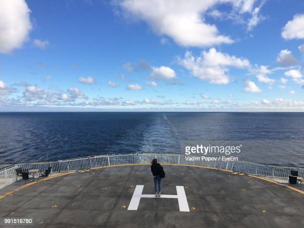 Woman Standing At Helipad In Ship On Sea Against Sky