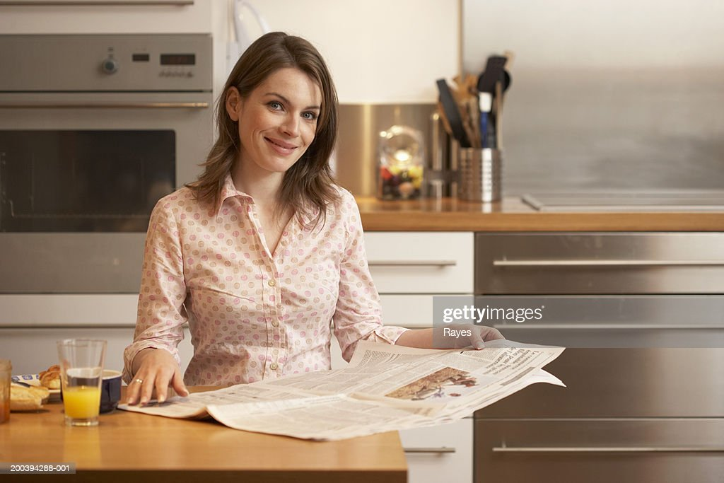 Woman standing at kitchen counter with newspaper, smiling, portrait : Stock Photo