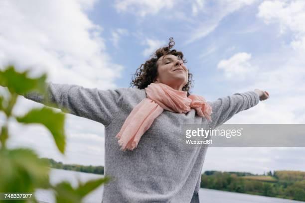woman standing at lake pretending to fly - einzelne frau über 30 stock-fotos und bilder