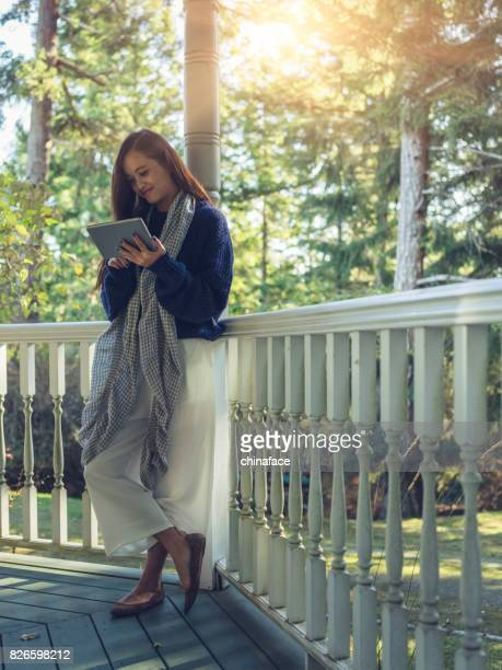 woman standing at porch,typing tablet - one young woman only stock pictures, royalty-free photos & images