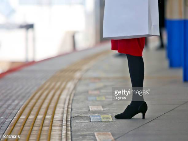 Woman standing at railway station platform waiting for train