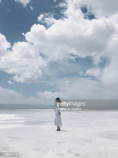 woman standing at salt lake against cloudy sky - liu he stock pictures, royalty-free photos & images
