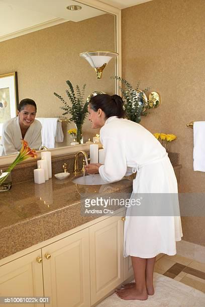 Woman standing at sink in bathroom