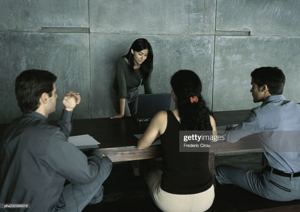 Woman standing at table looking at computer, three people sitting at table. : Stockfoto