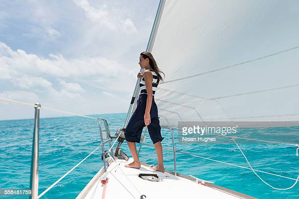 woman standing at the bow of sailboat - hot women on boats stock pictures, royalty-free photos & images
