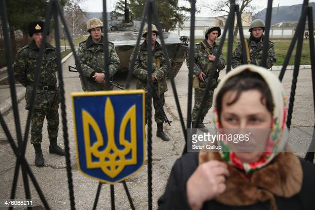 Woman standing at the gate outside a Ukrainian military base that was surrouneded by several hundred Russian-speaking soldiers crosses herself after...