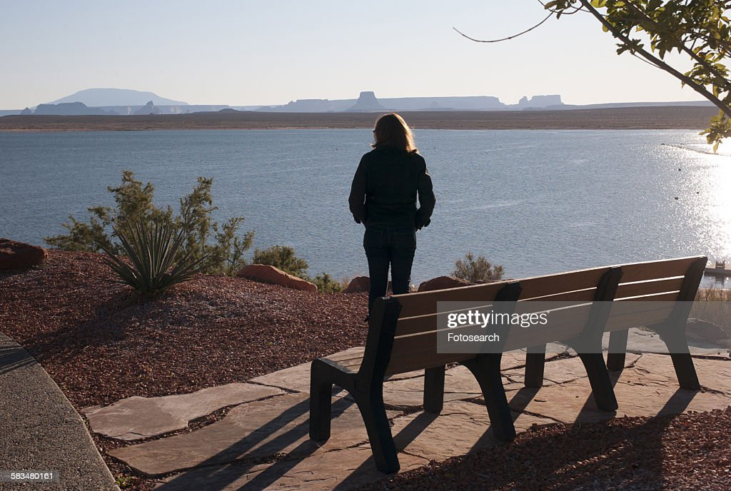 Woman standing at the lakeside : Stock Photo