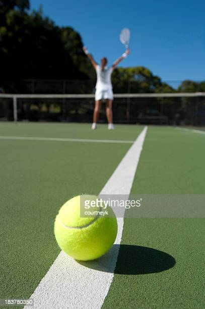 Woman standing at the net with arms raised
