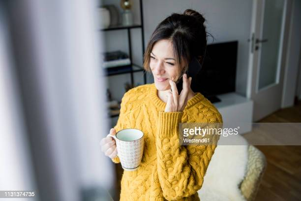 woman standing at the window, drinking tea, talking on the phone - am telefon stock-fotos und bilder