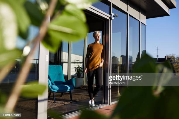 woman standing at the window on roof terrace - time of day stock pictures, royalty-free photos & images