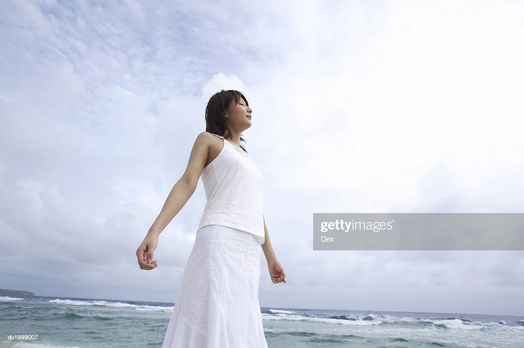 Woman Standing at Water's Edge With Her Eyes Closed and Arms Out : Stock Photo