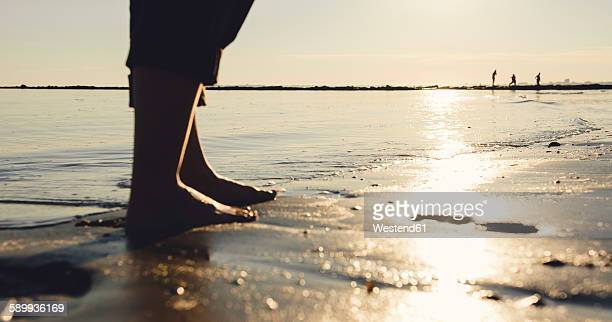 Woman standing barefoot at seashore by evening twilight, close-up
